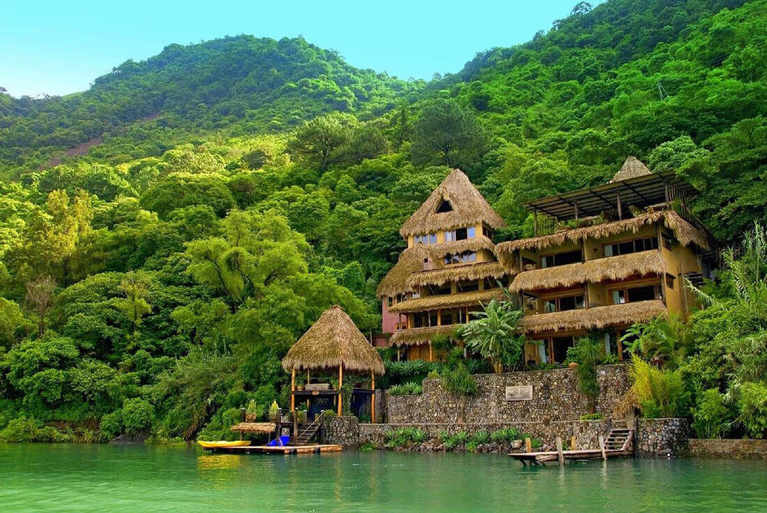 large bamboo hut on a river in a tropical forest