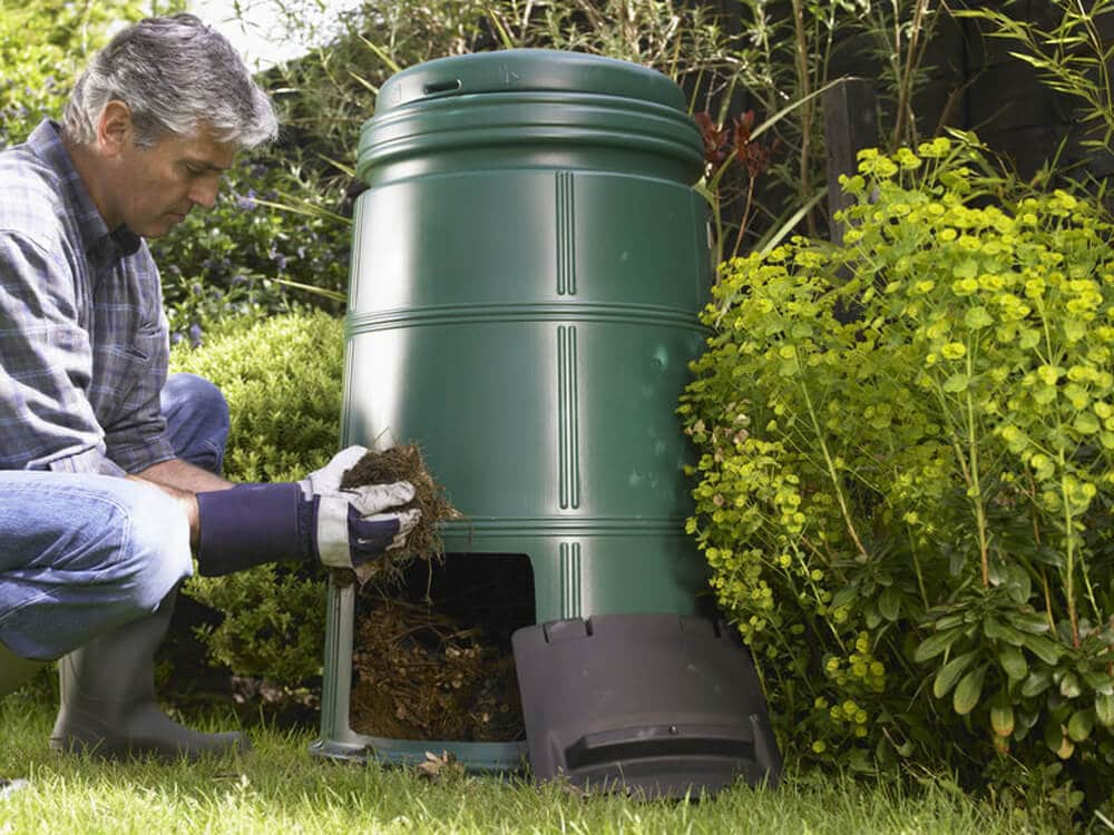 man removing compost from compost bin