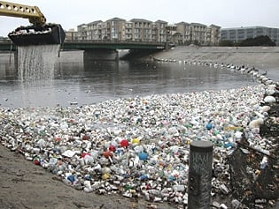 thousands of plastic bottles washed up on a riverbank