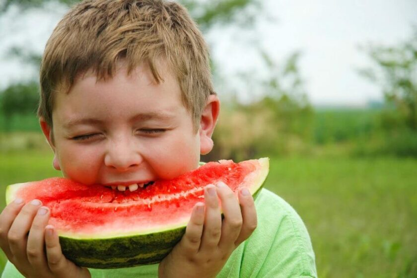 boy keeping cool by eating watermelon