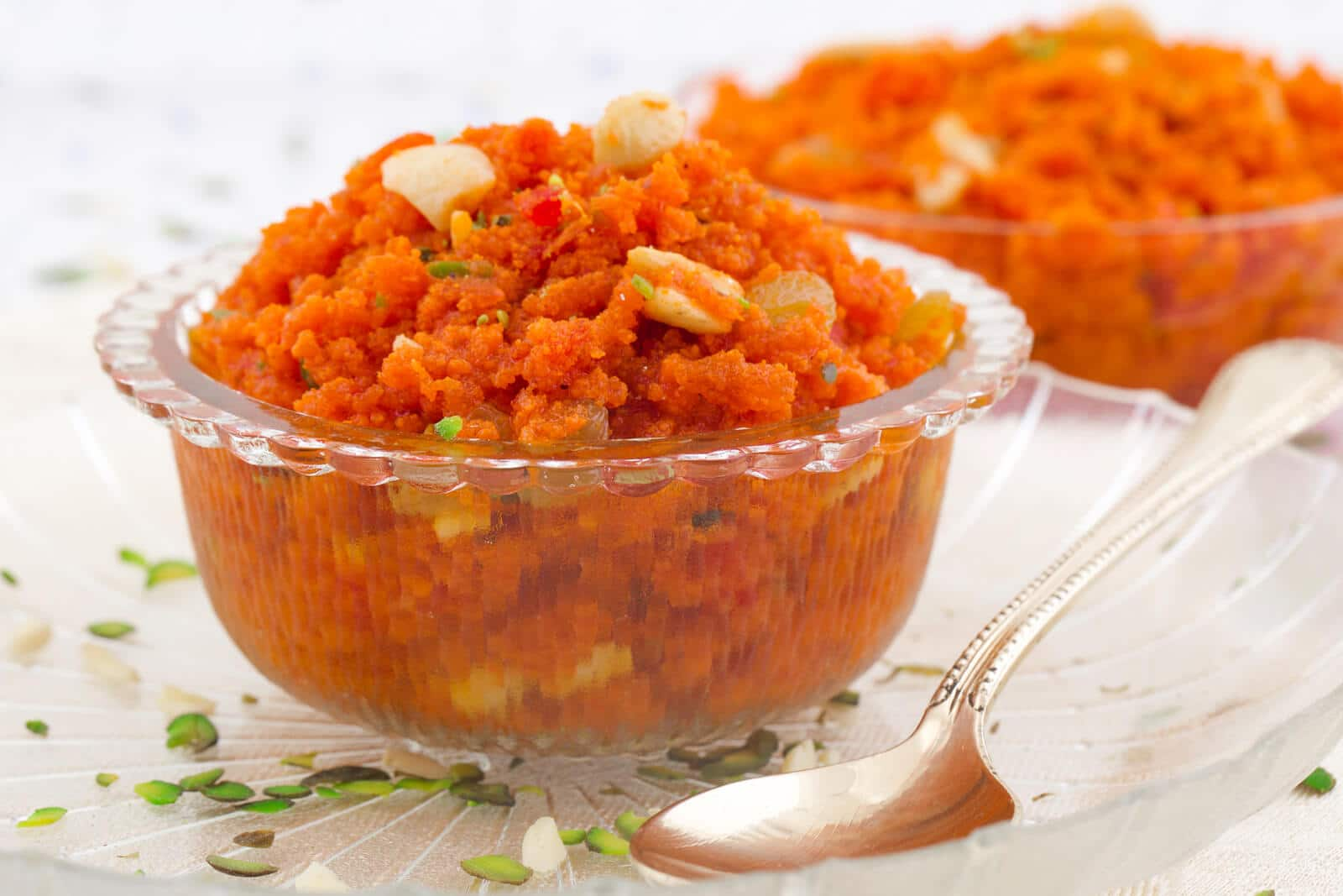 carrot halwa dessert in a glass bowl with a spoon on a white counter