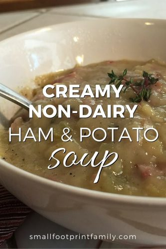 creamy ham and potato soup in a bowl with a spoon on a table