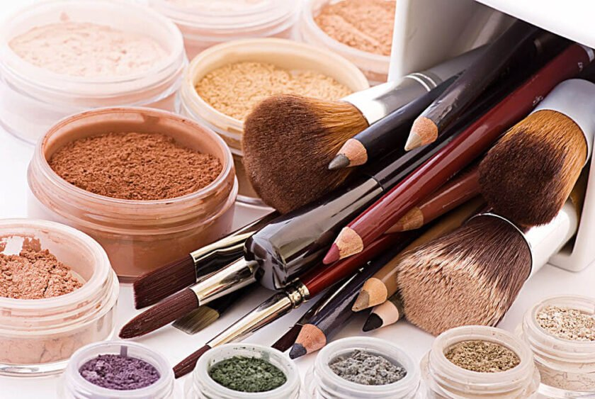 eyeshadows, eyeliners, powders, brushes and other make up on a countertop