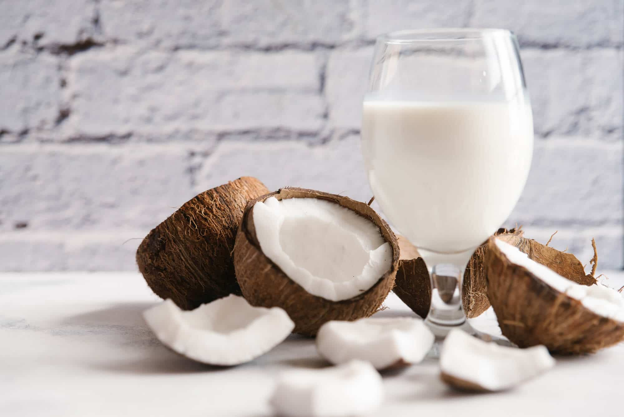 Coconut milk with broken coconut on white table