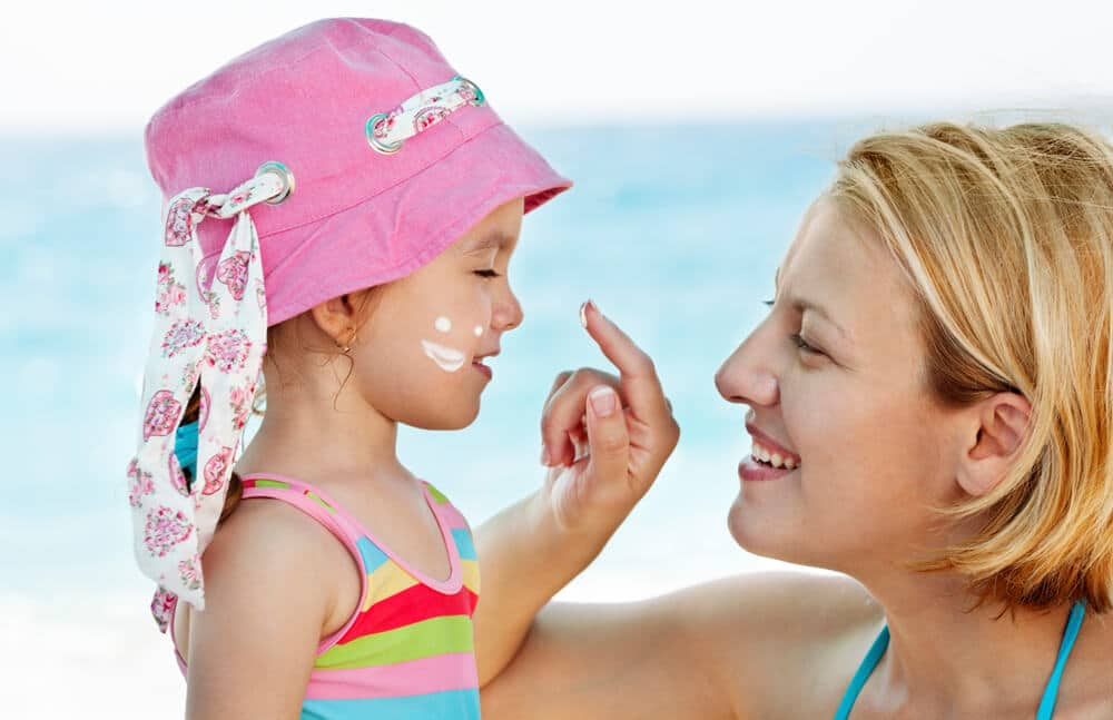 mother applying sunscreen to little girl's nose