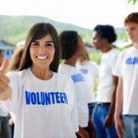"""woman wearing a white t-shirt that says """"Volunteer"""" in blue letters"""
