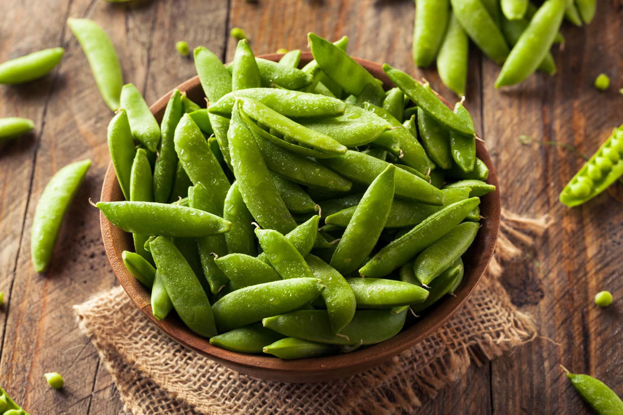 snap peas in a wooden bowl on a wooden countertop