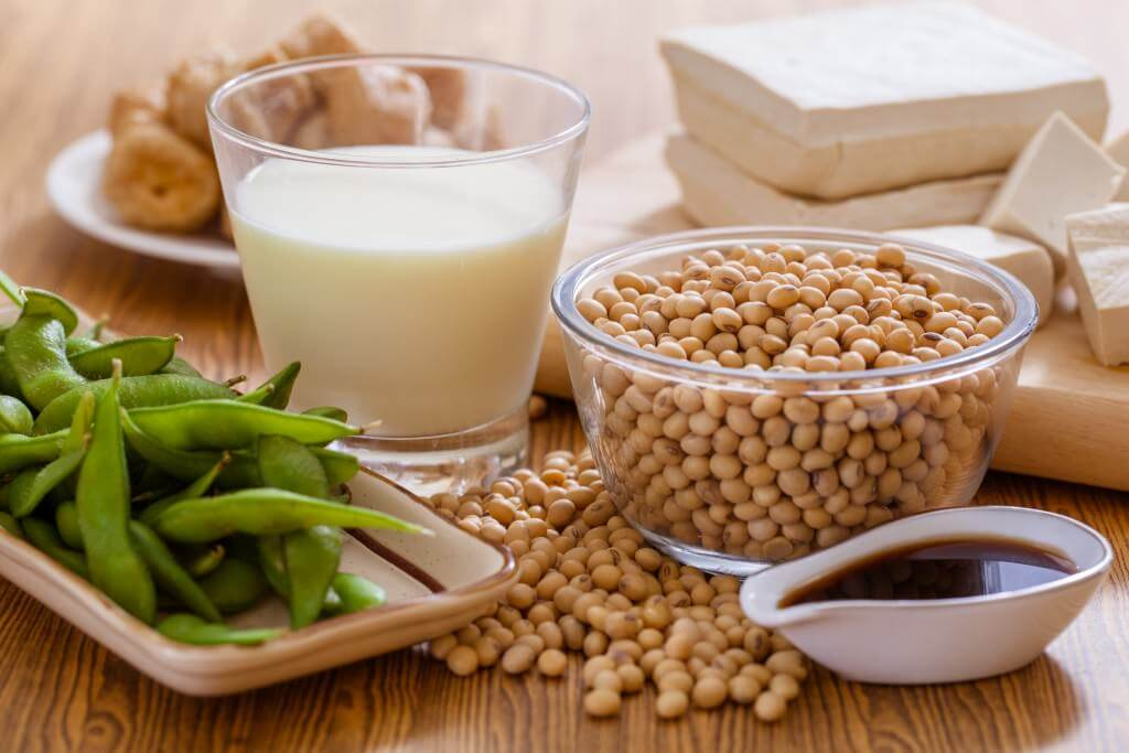 tofu, soymilk, soybeans, edamame, and soy sauce on a table