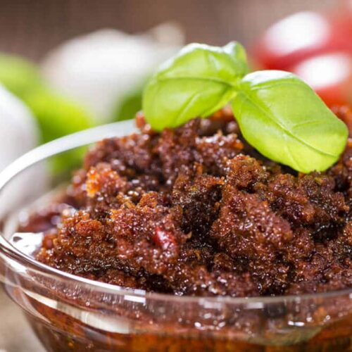 sun dried tomato pesto in a glass dish on a table, garnished with basil