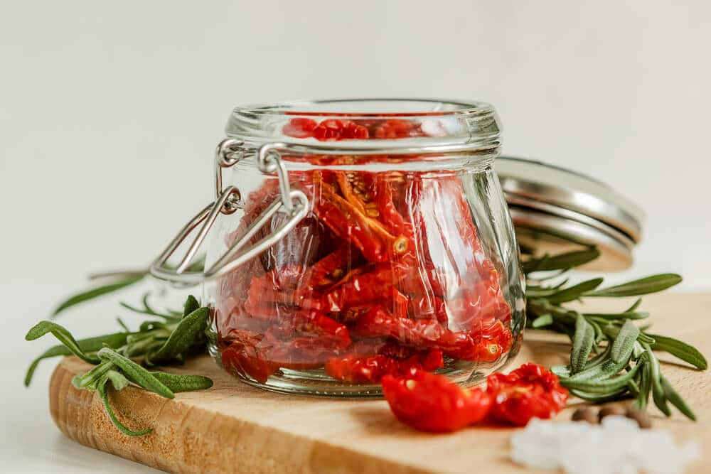 sun dried tomatoes in a jar next to rosemary, salt and garlic on a table