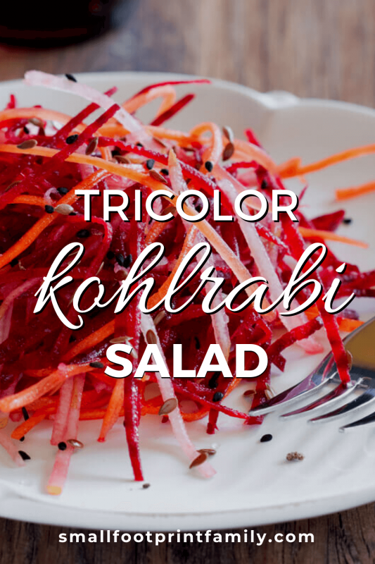 white plate on a wood table with beet, carrot and kohlrabi slaw on it next to a purple handled fork