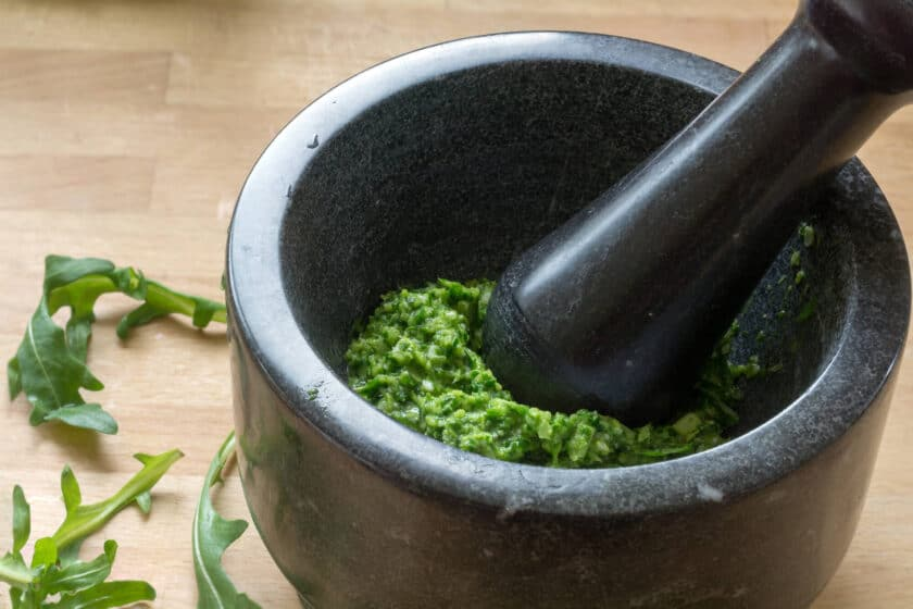 pesto in a black mortar and pestle with arugula leaves on the table