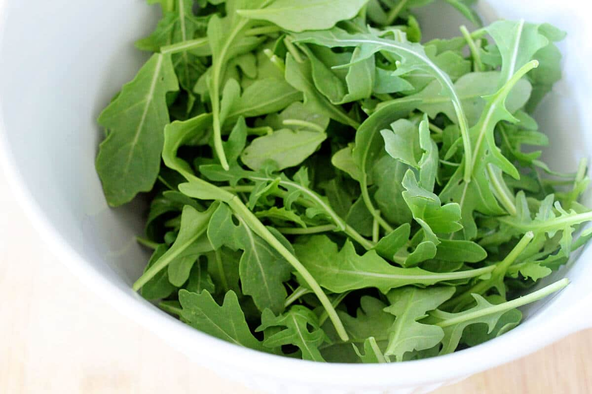 white bowl full of arugula