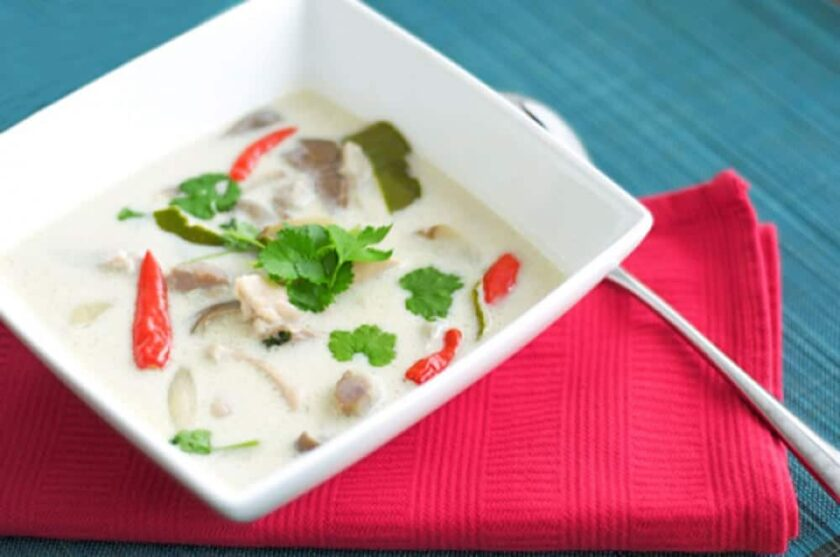 Tom kha gai soup in a square, white bowl on a red napkin