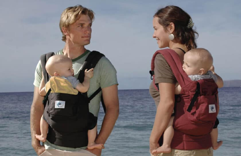 A man and a woman both carrying babies on their backs using babywearing slings
