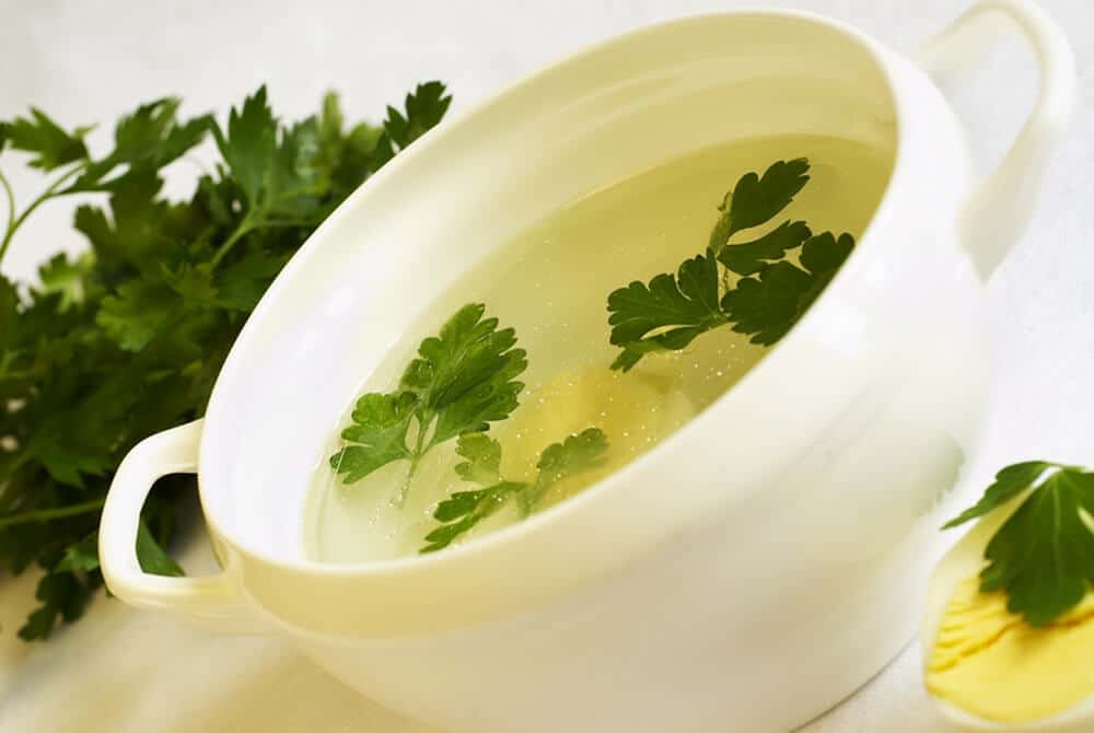 chicken broth in a white bowl garnished with parsley