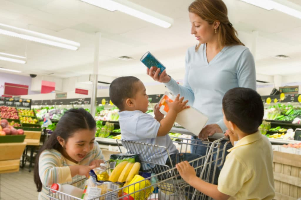 mom with three kids in a shopping cart reading product labels in a grocery store