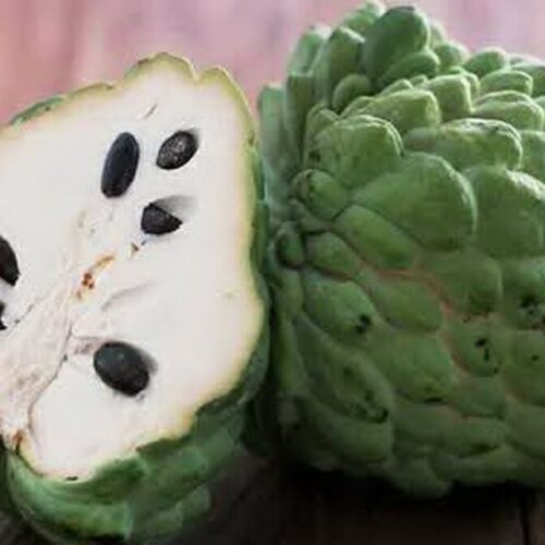 cherimoya cut in half on a wooden table
