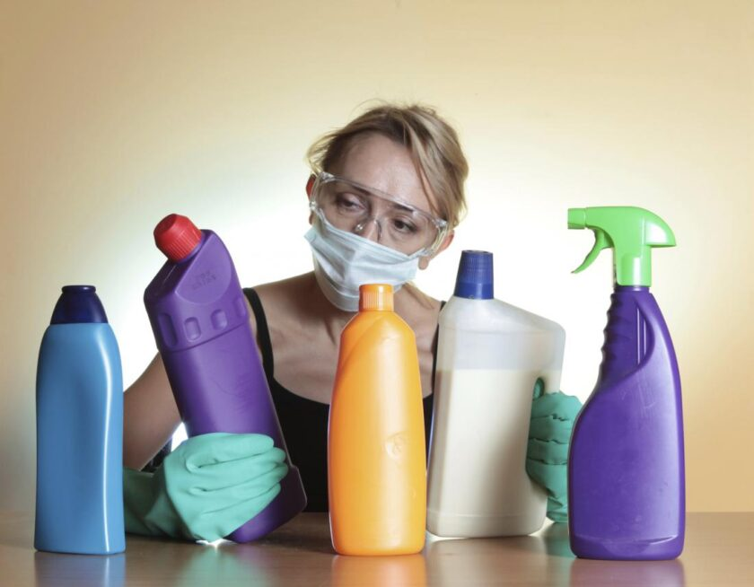 woman in mask looking at bottles of household chemicals