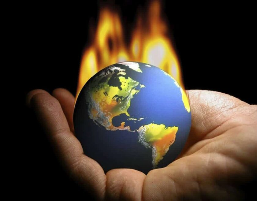 hand holding a planet Earth model that is on fire