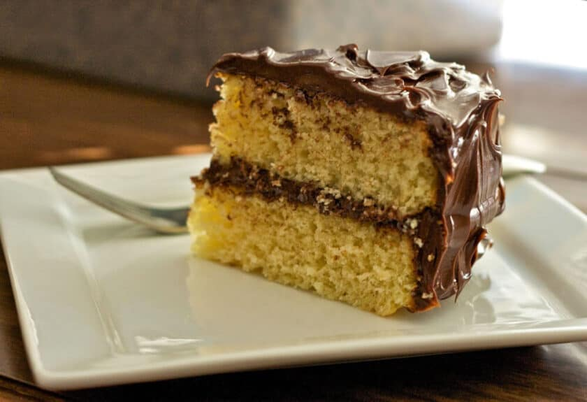 slice of gluten-free vanilla layer cake with vegan chocolate frosting on a white plate
