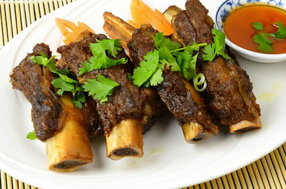 pork spare ribs seasoned with Chinese 5-spice on a plate with cilantro garnish