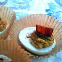 deviled eggs with bacon and dill in a cupcake wrapper on a table