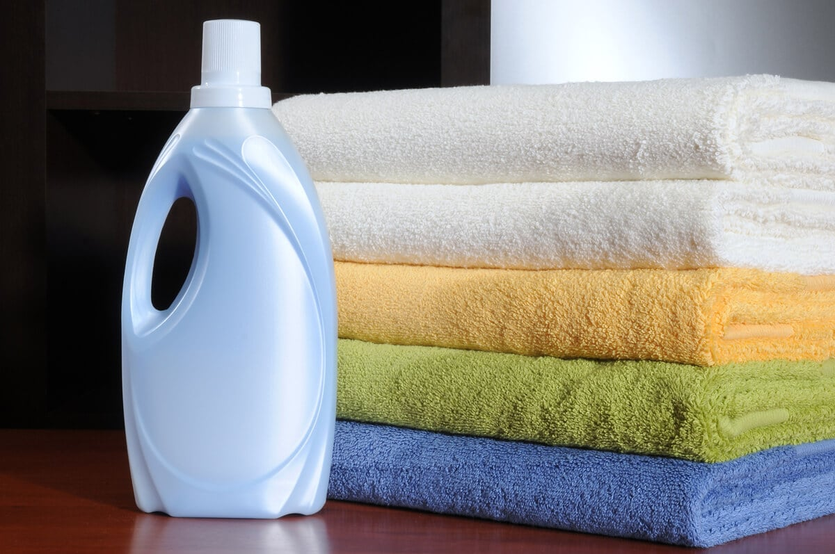 bottle of laundry detergent next to a stack of clean towels