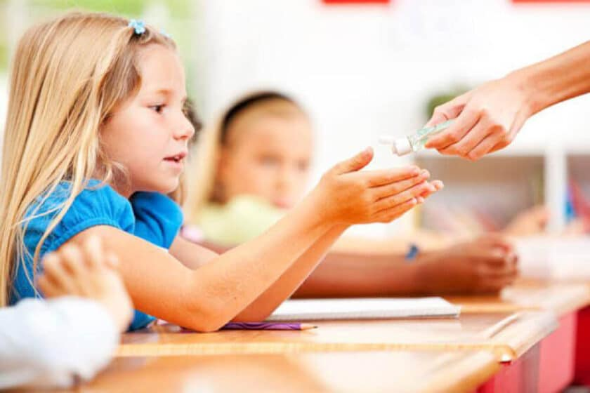 child holding out hands to receive hand sanitizer