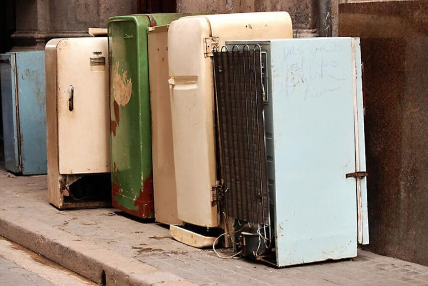 a row of old refrigerators in a junkyard