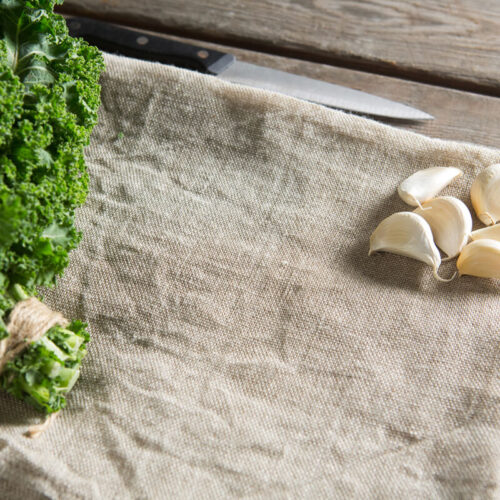 kale leaves and garlic cloves on a burlap napkin on a table