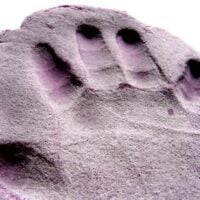 child's handprint in purple homemade gluten free play dough on a white table