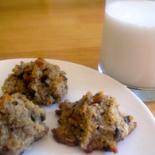 Old fashioned cookies on a white plate with a glass of milk next to it