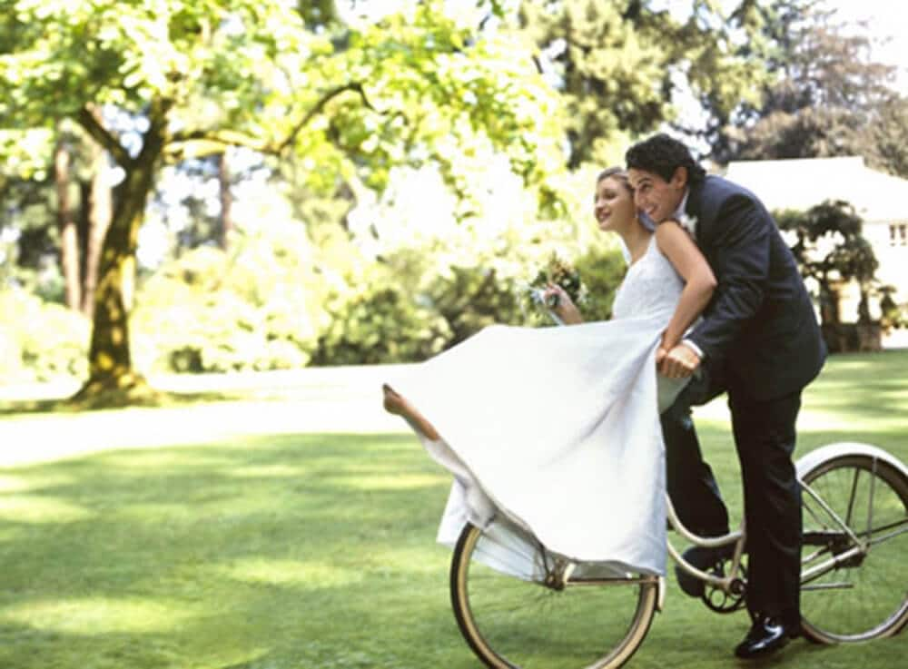 bride and groom on a bicycle