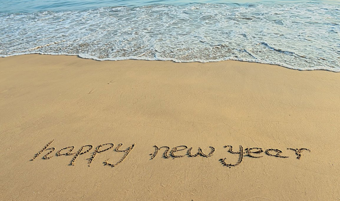 beach with happy new year written in the sand