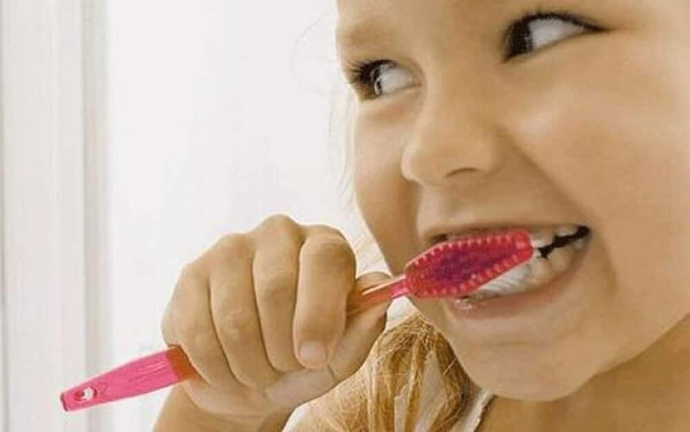 child with red toothbrush brushing teeth