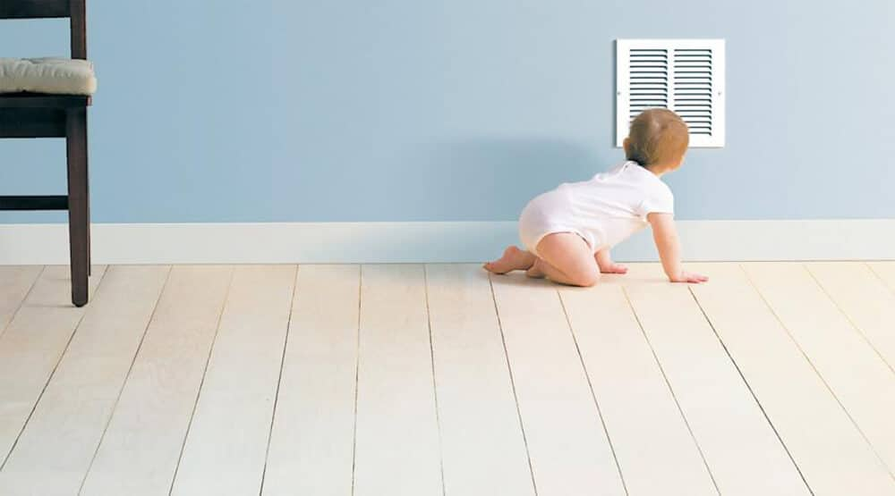 baby on a wood floor looking into an air vent