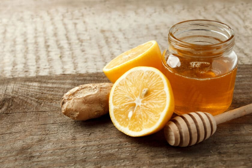 lemon, ginger and a glass jar of honey on a wooden table