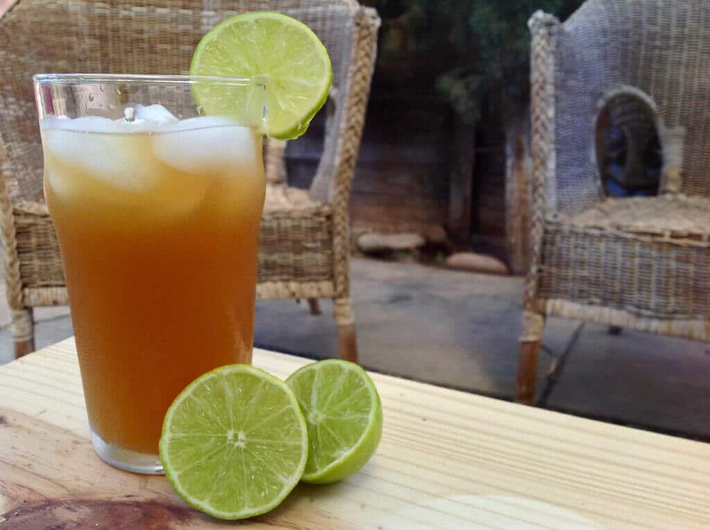 glass of honey sweetened limeade with sliced lime on a table