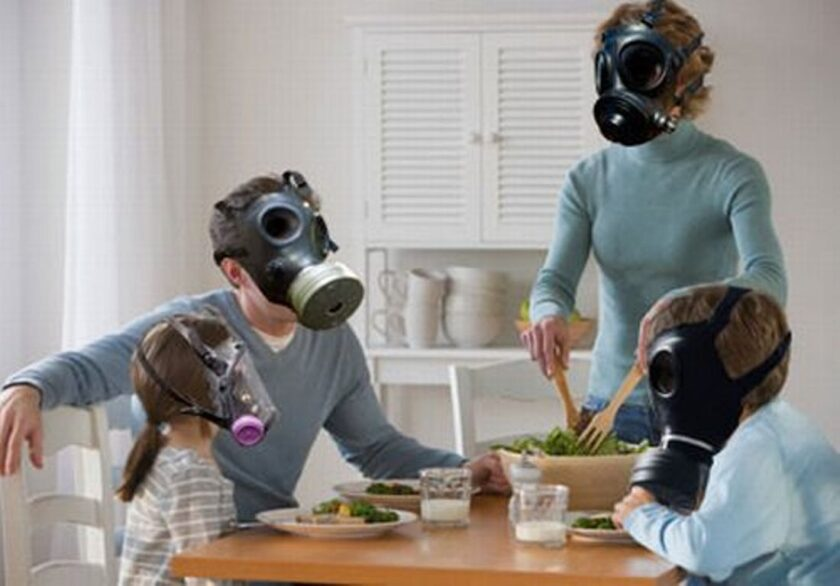 family at the dinner table wearing gas masks