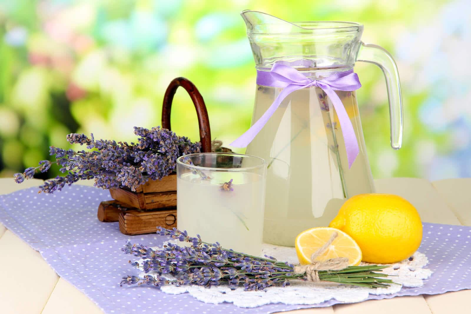lavender lemonade in a pitcher on a table with lemons and lavender blossoms