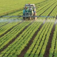 plow spraying chemicals on a monoculture of soybeans