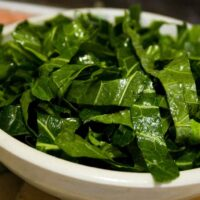 mustard greens with garlic mayonnaise in a white bowl