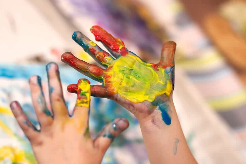 kids hands covered with homemade gluten free finger paint
