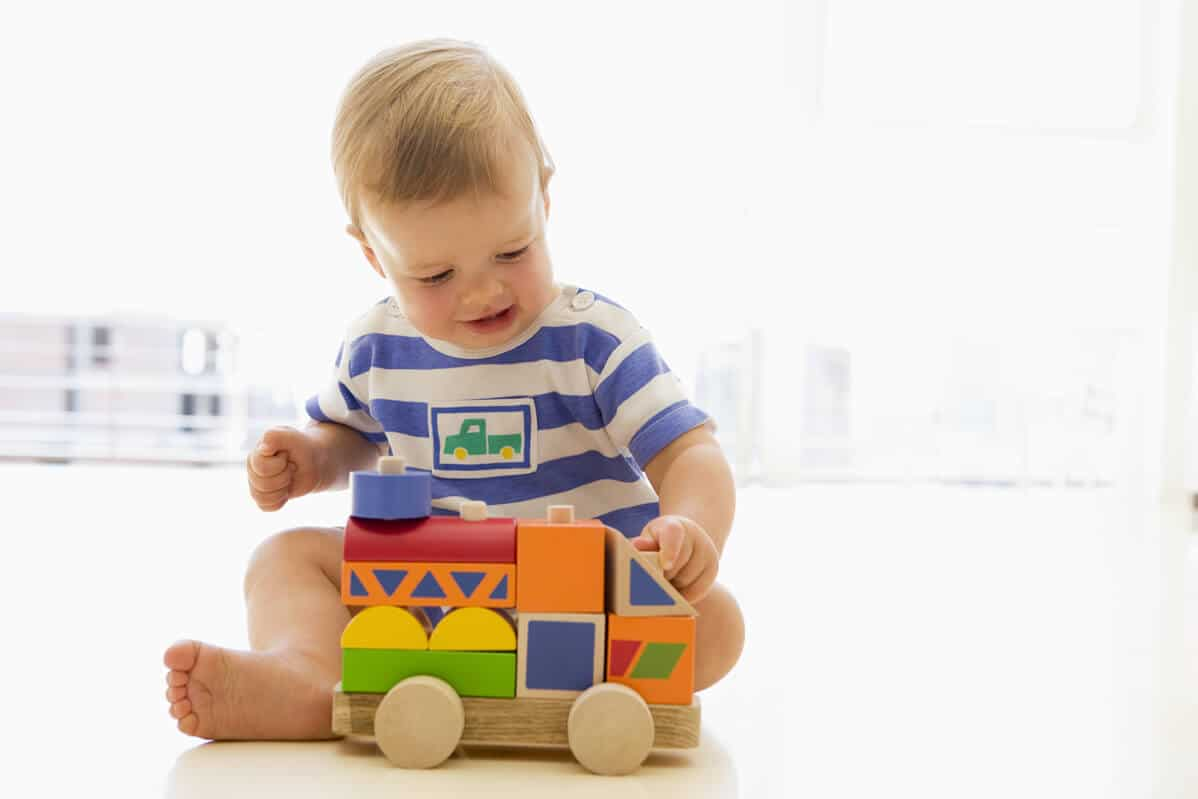 child playing with wooden block toys