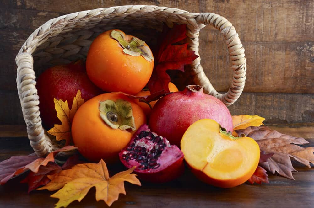 pomegranates and persimmons in a basket