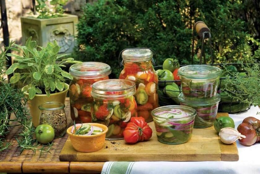 canning jars full of pickles on a wooden table outdoors.