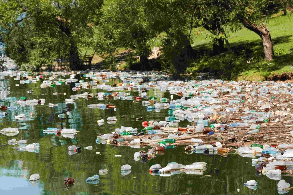 hundreds of water bottles littering the shores of a lake