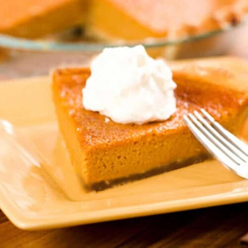 raw sweet potato pie on a plate with a fork and whipped cream