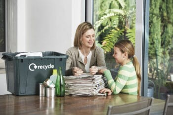 mother and child with a stack of newspapers and a recycling bin